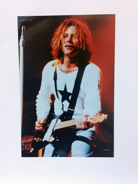 "6 x 4"" photograph of Jon Bon Jovi on Stage, wearing White Sweatshirt with Black star"